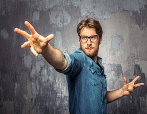 גבר צעיר ואלגנטי עושה תנועת כישוף בידיו