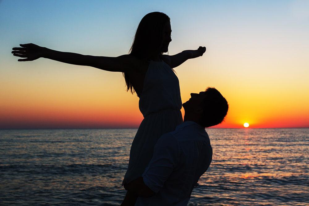 זוג בים ,גבר מרים אישה ואישה פורסת ידיים